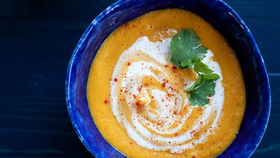 A blue ceramic bowl filled with red lentil carrot soup.