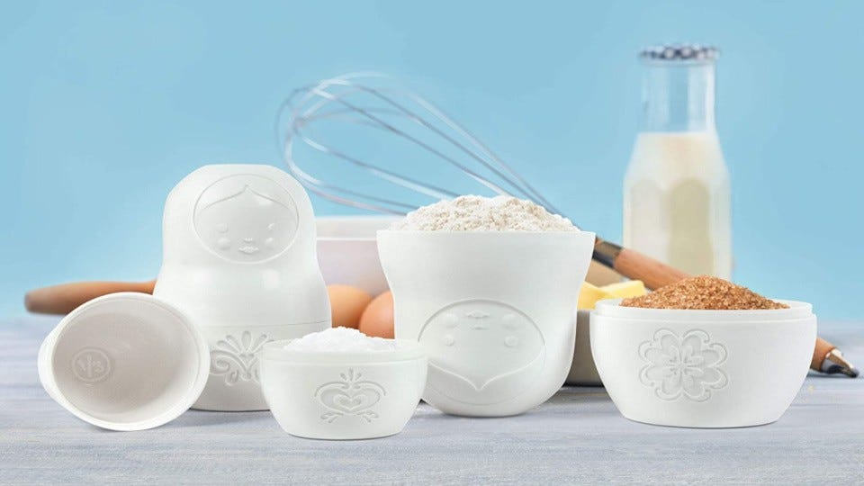 A set of white Matryoshka doll measuring cups, filled with ingredients displaying a whisk, eggs butter and milk in the background.