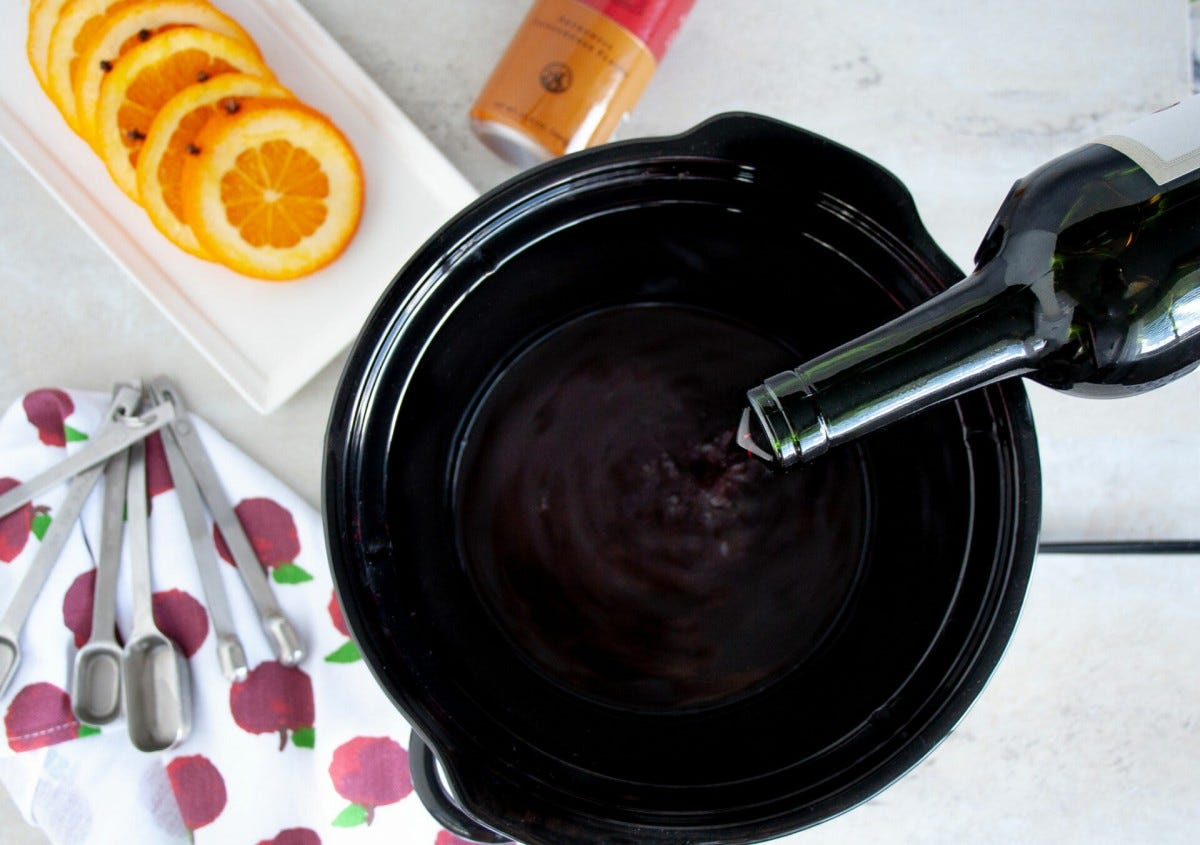 A bottle of wine being poured into a slow cooker, with a plate of sliced oranges nearby.