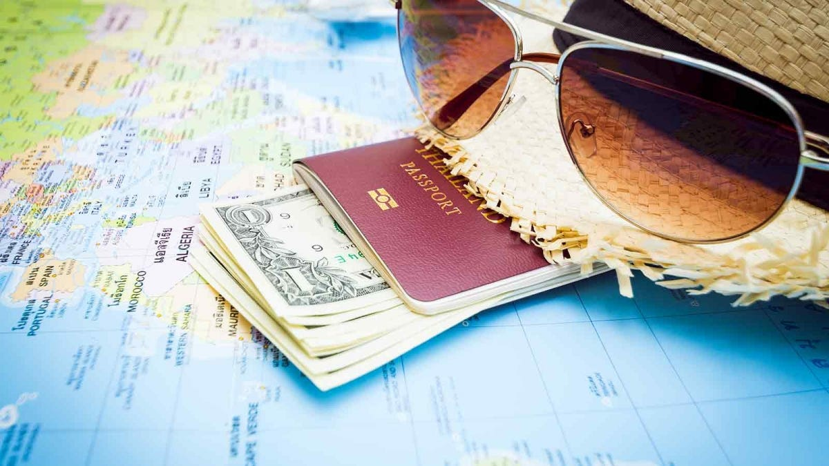 Sunglasses, a sun hat, a passport, and money sitting on top of a world map.