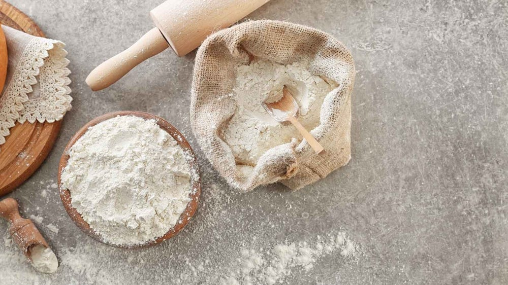 A bag and bowl of flour on a counter next to a rolling pin.