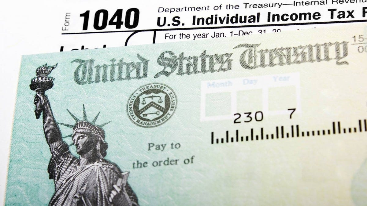 A check from the U.S. Treasury imposed over tax forms.