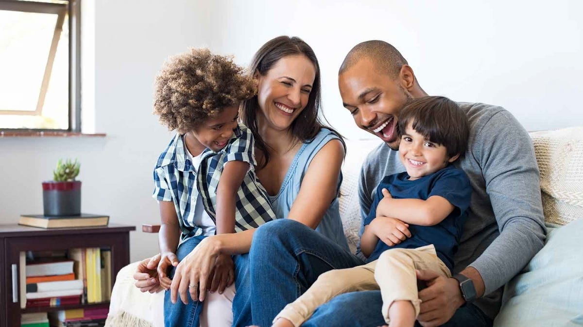 Family laughing together on a couch in a brightly lit living room