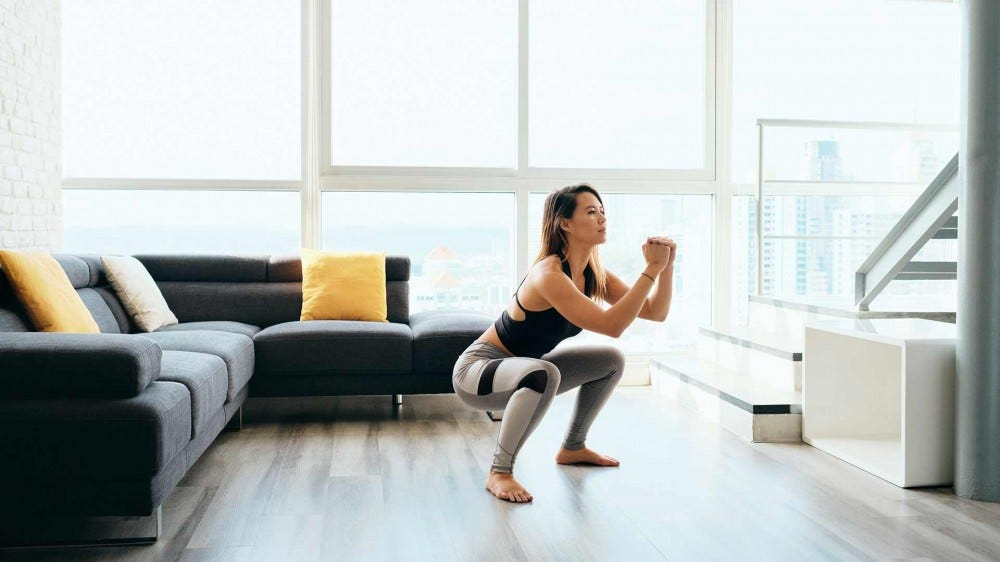A woman doing squats at home as part of a HIIT workout routine.