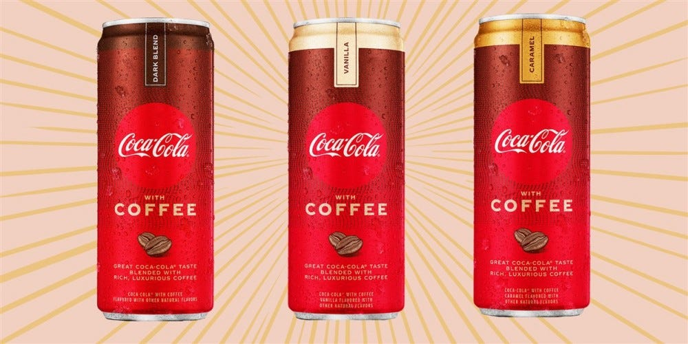 Three cans of Coca-cola with coffee stand together.