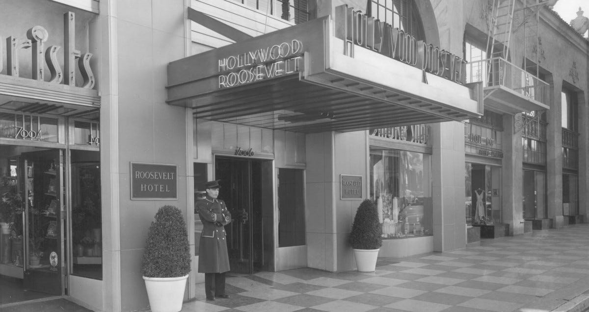 a 1950s era photograph of the exterior of the Hollywood Roosevelt, doorman in attendance