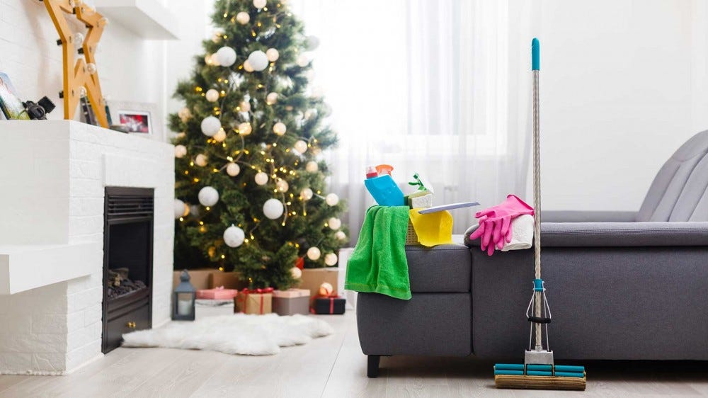 A mop leaning against the side of a couch in a living room decorated for Christmas.