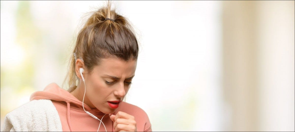 Young woman wearing workout sweatshirt sick and coughing