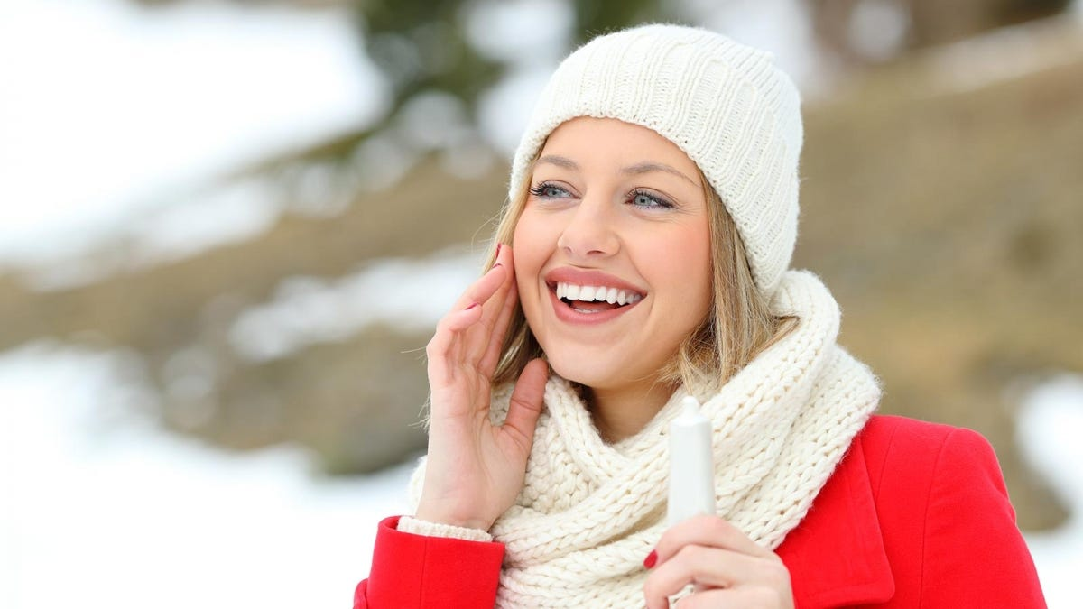 woman putting a moisturizer containing sunscreen on her face before heading out to enjoy winter activities