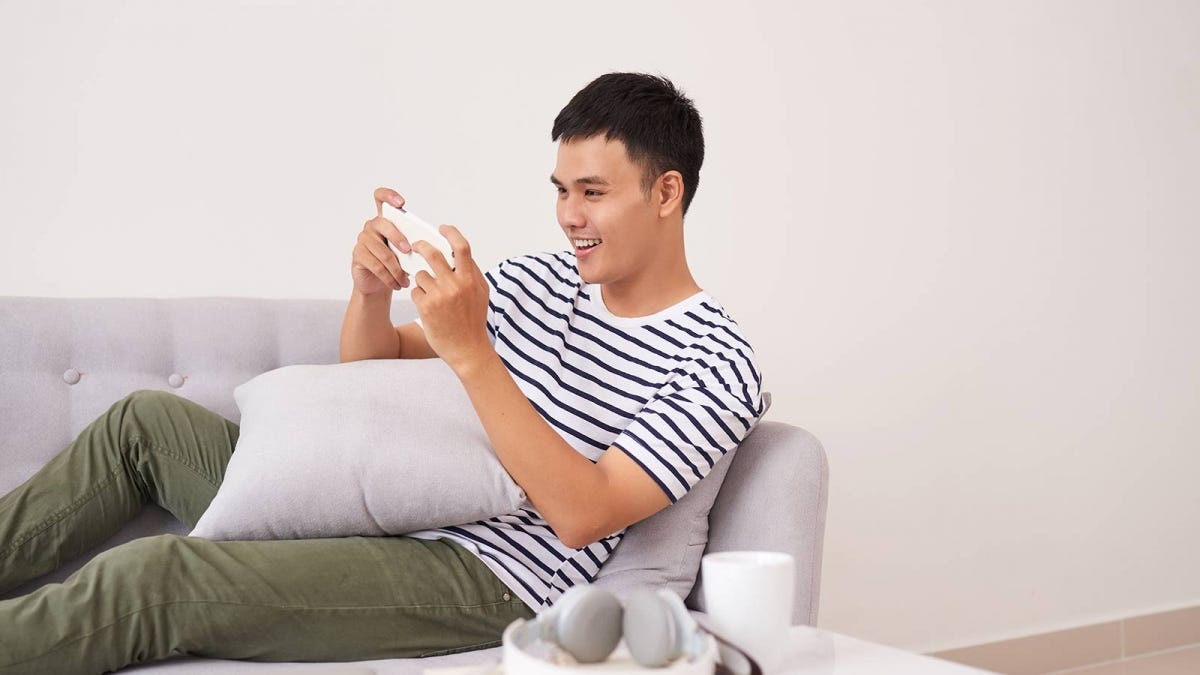 Man laughing while watching a funny video on his phone.