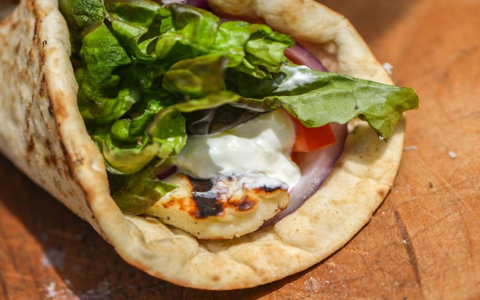 A pita sandwich stuffed with halloumi cheese, tomato, lettuce and red onion.