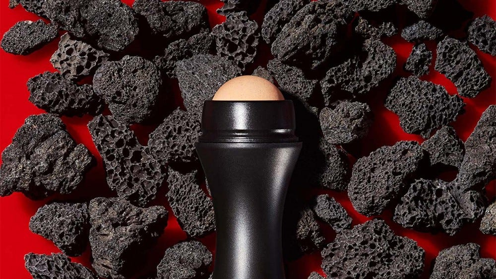 A Revlon volcanic roller resting on a pile of volcanic pumice stone.