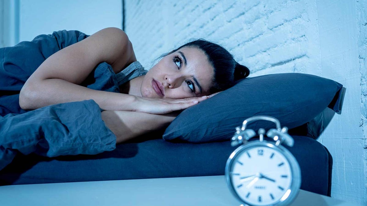 Woman in bed staring at the ceiling, next to a bedside table with a clock sitting on it.