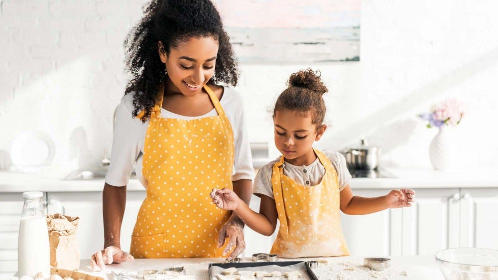 A mother and a daughter baking together in a brightly lit kitchen.