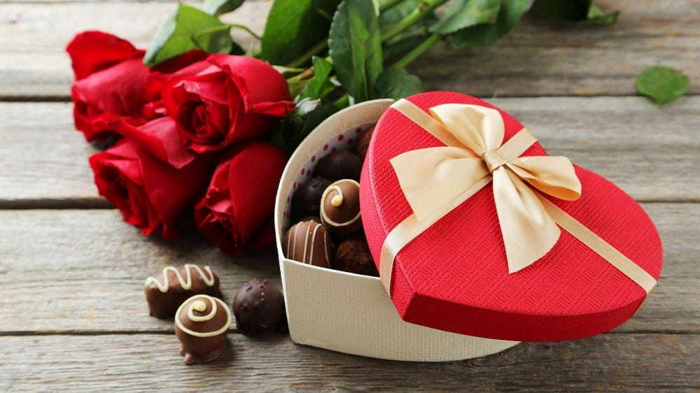 A box heart-shaped box of Valentine's Day candies, with roses, on a wooden table.