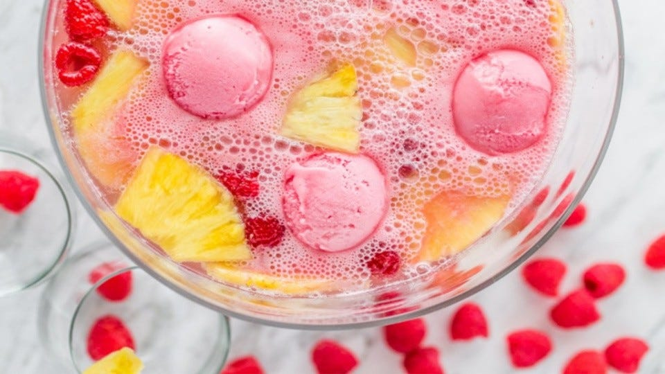 A punch bowl filled with party punch with floating raspberries, pineapple and scooped sherbet ice cream.