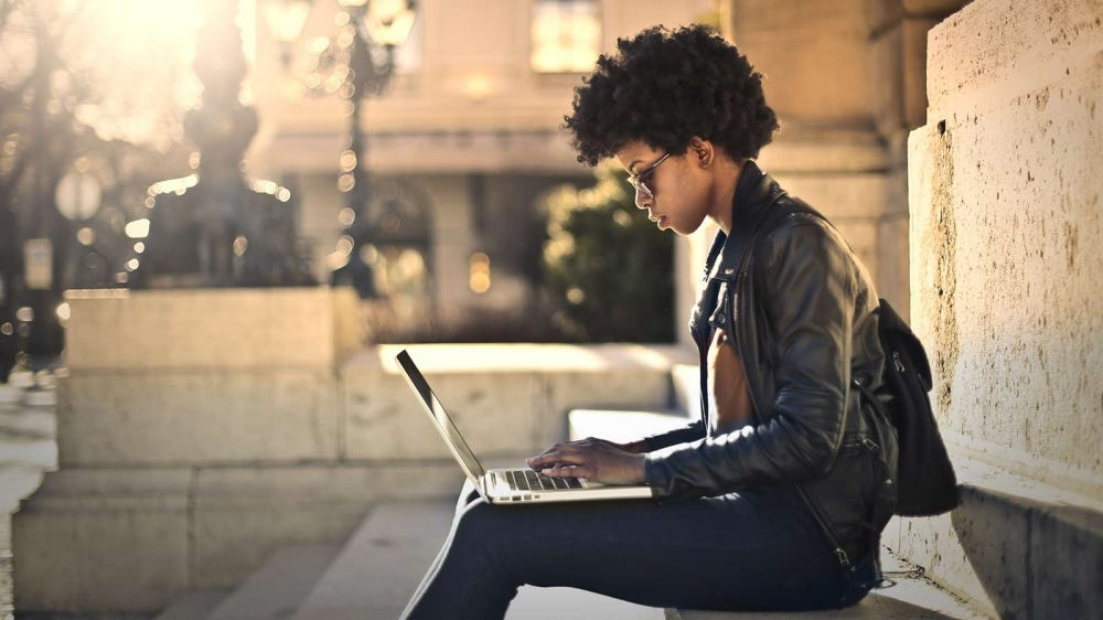 A woman working outside with her laptop, adding some updates to her resume.