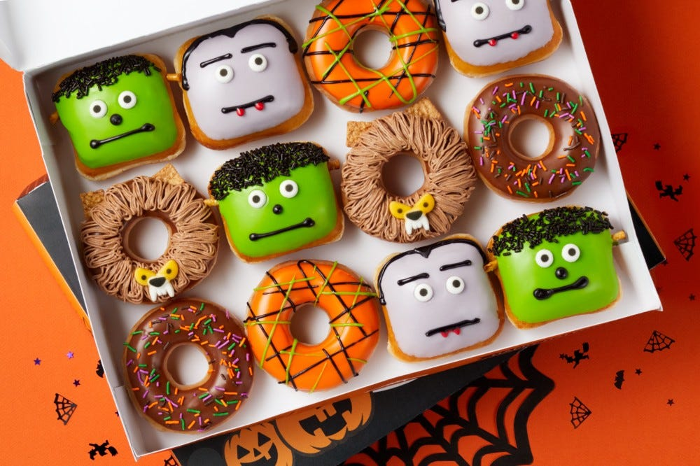 A collecion of a dozen doughnuts decorated to look like Frankenstein's monsters, Dracula, and a werewolf sit in a container.