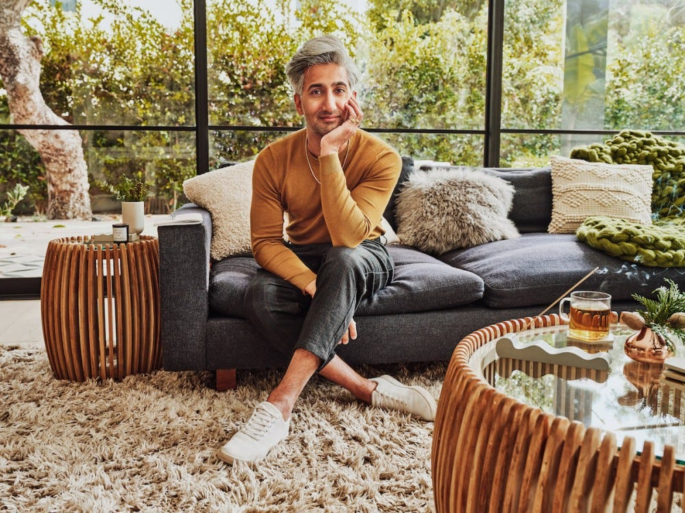 Tan France sitting on a navy couch surrounded by pieces from his new Home Goods line.