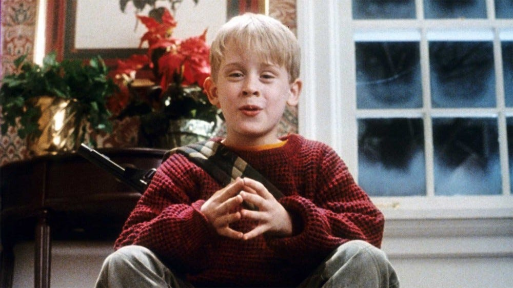 Kevin McCallister, the main character of 'Home Alone' sitting at the top of the stairs taunting the villains in the film.