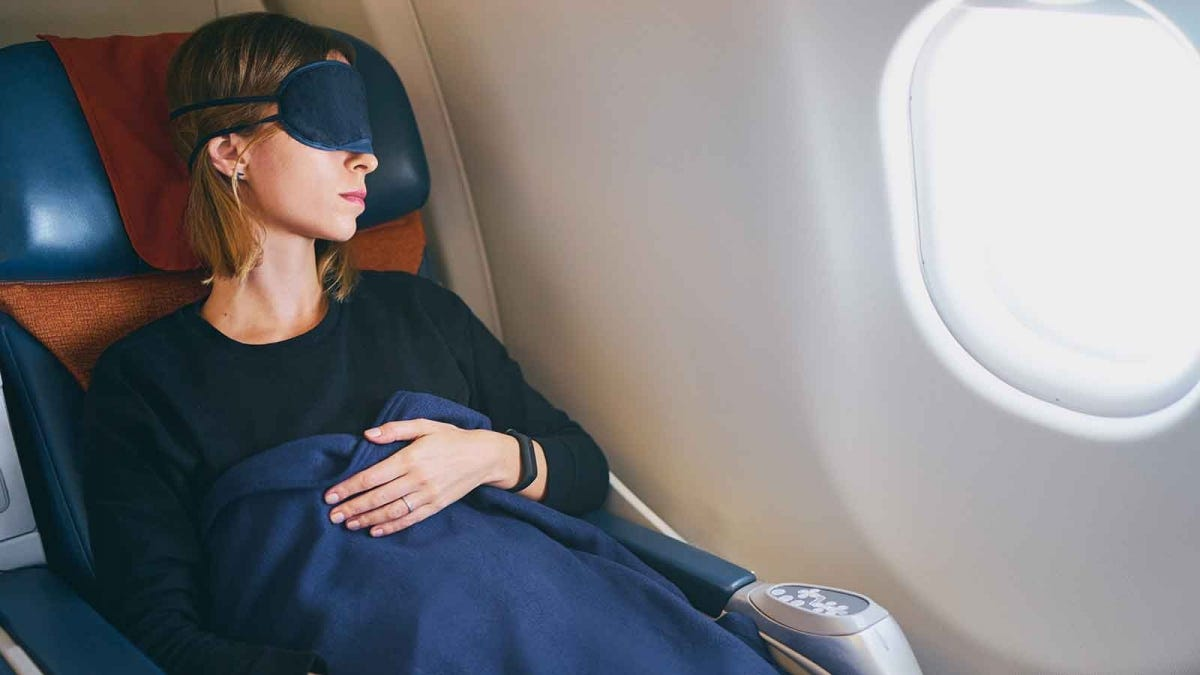 Woman sleeping on a plane with a blanket and eye mask.