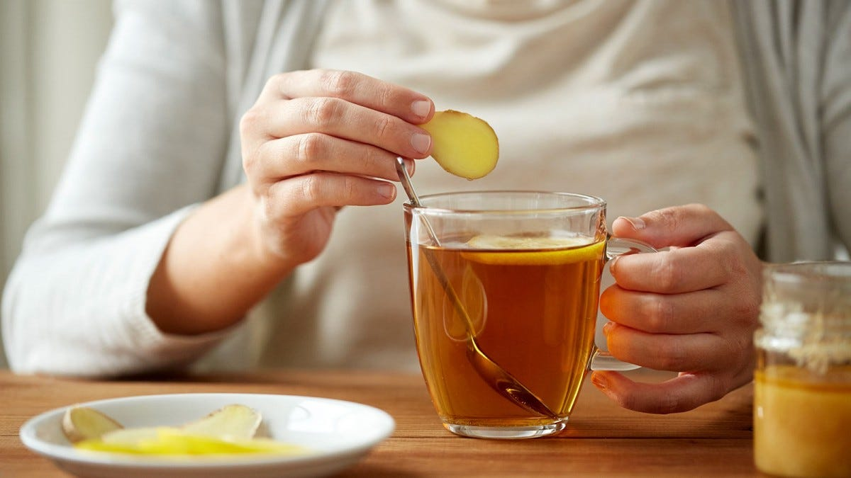 close up of woman adding ginger to tea cup with lemon and honey