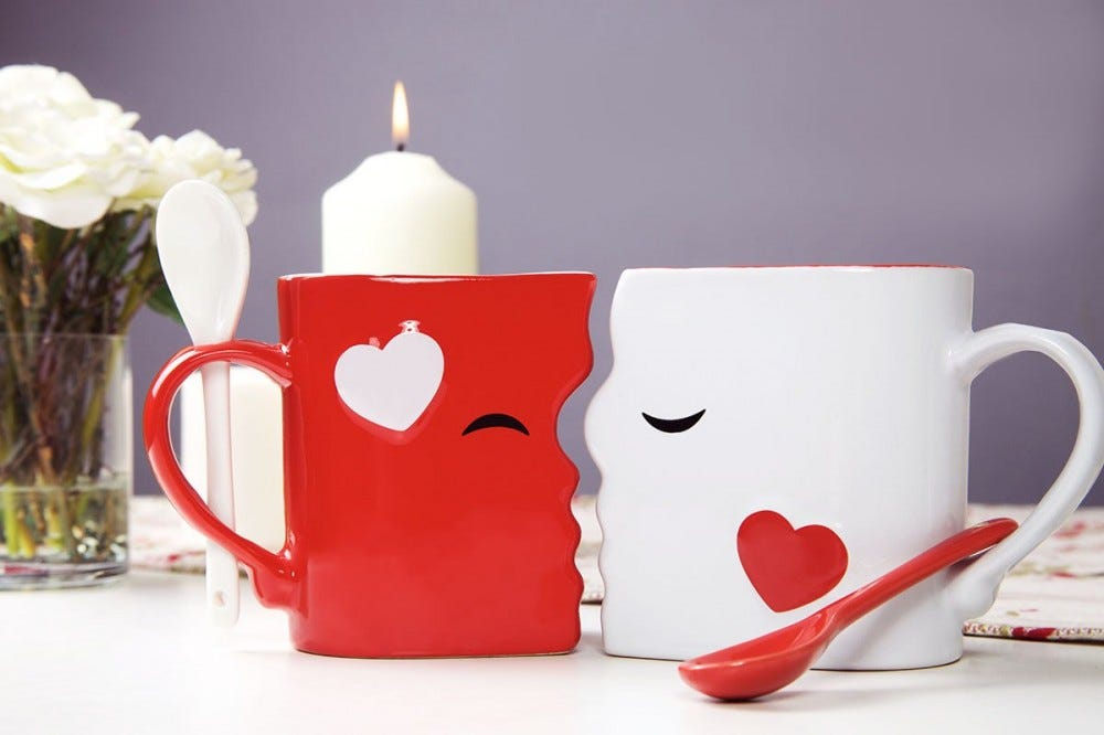 Two mugs, designed so that they look like they are kissing each other.