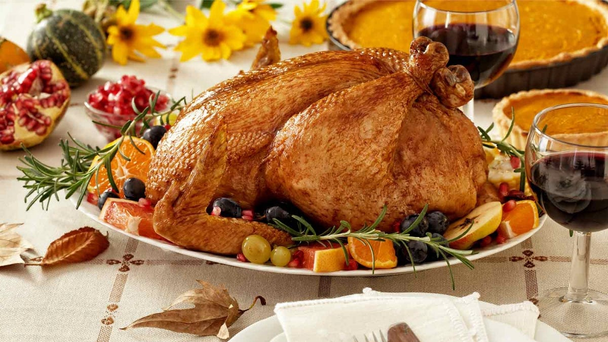 a turkey, prepared with brine and well roasted, resting on a table surrounded by food