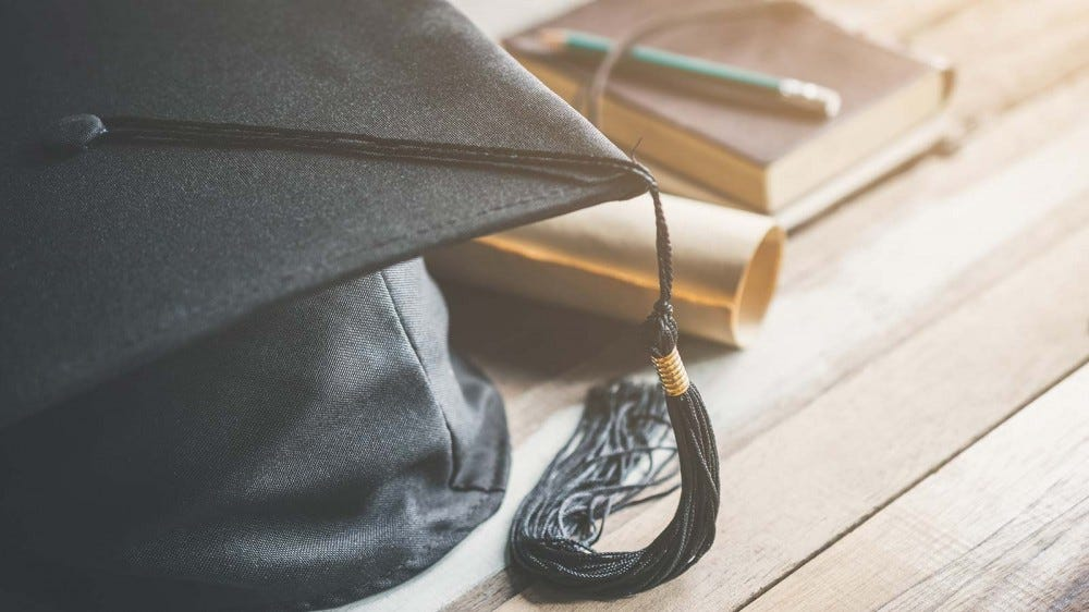 A graduation cap sitting on a table next to a book and diploma.
