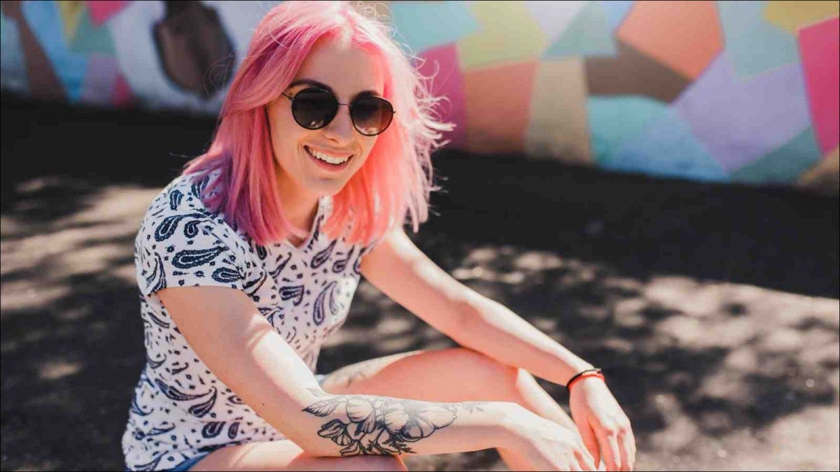 young woman with pink shoulder-length hair smiling in sunlight