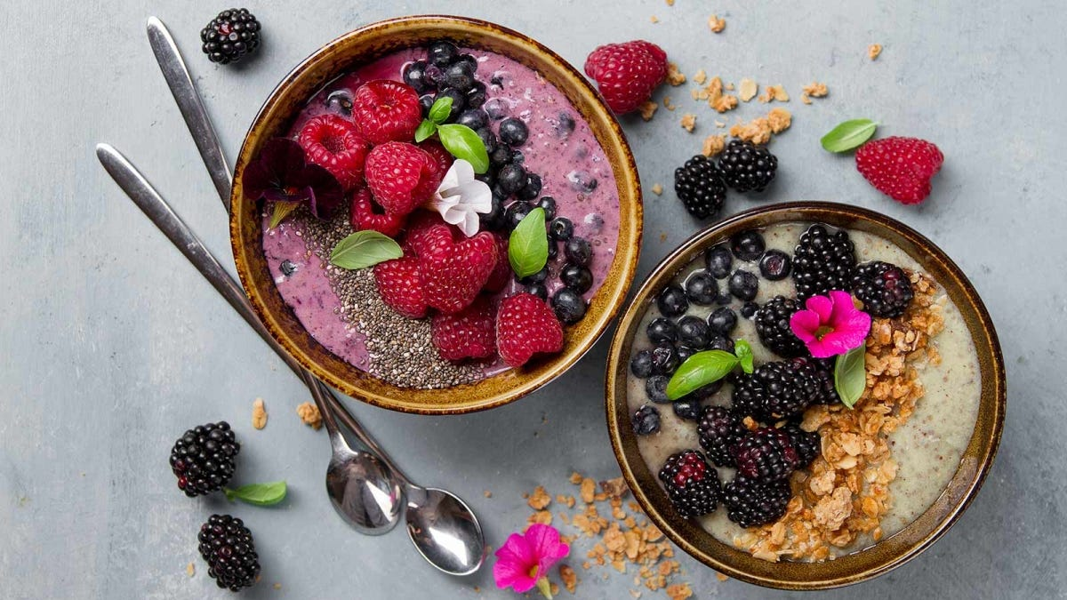 Breakfast smoothie bowls with fruit, oak flakes, and seeds.