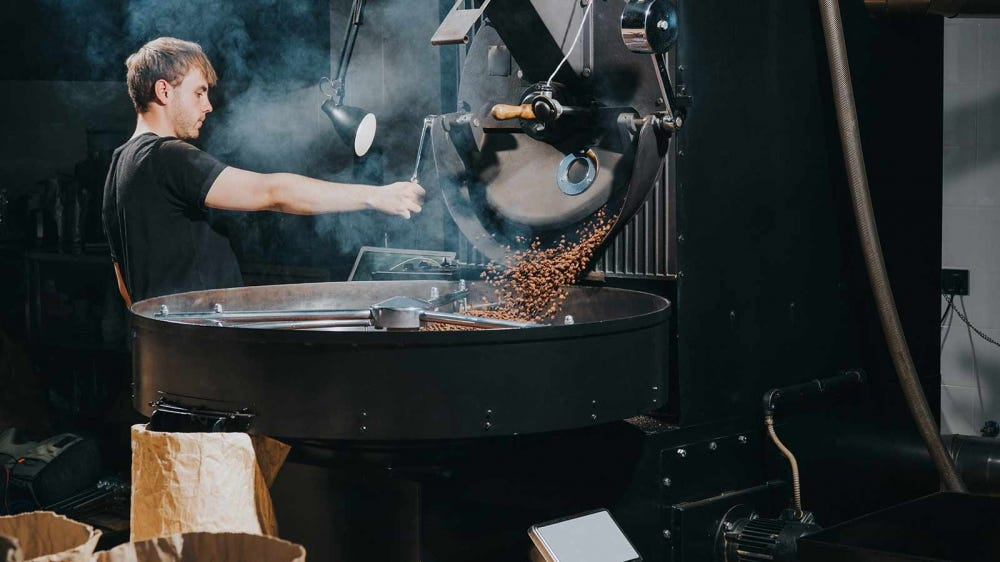 A man roasting coffee beans in a large industrial roaster.