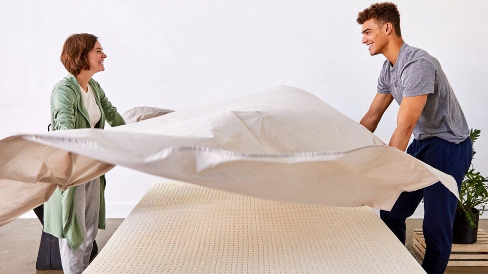 A man and woman spreading a sheet over a Pure Green mattress topper.