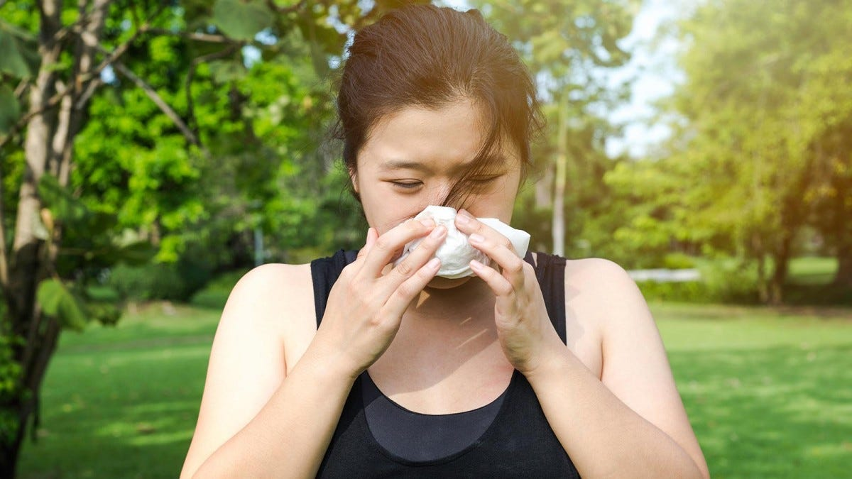 Woman blowing her nose while exercising in the park despite being sick.