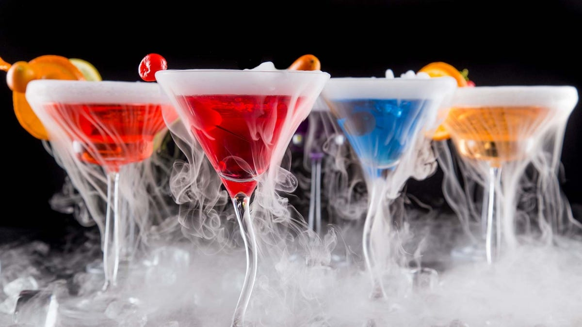 Four colorful cocktails with fog rolling off the tops.