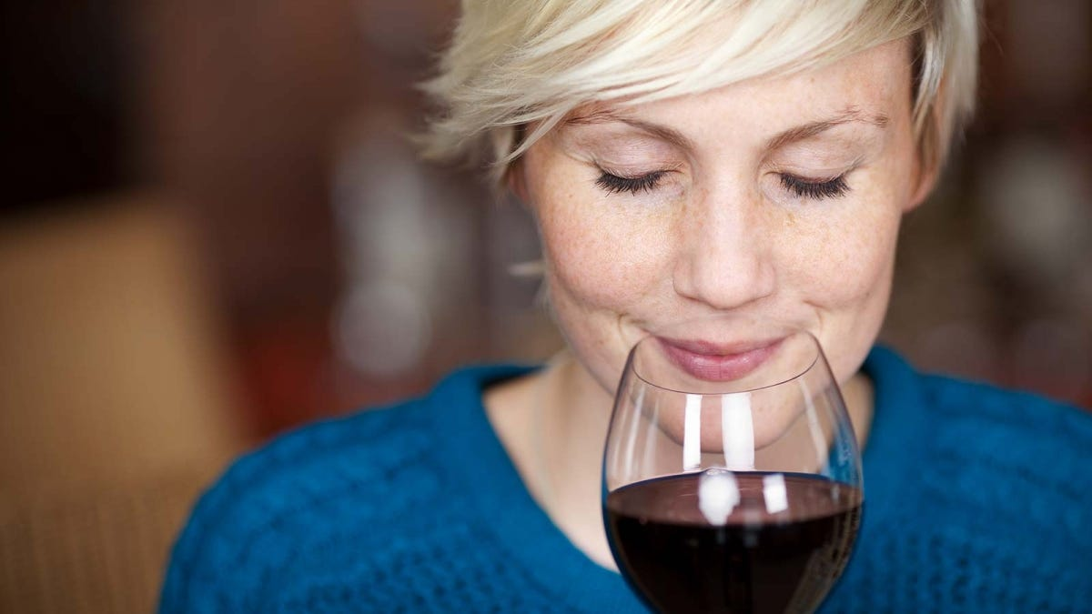 A woman smelling a glass of red wine with her eyes closed.