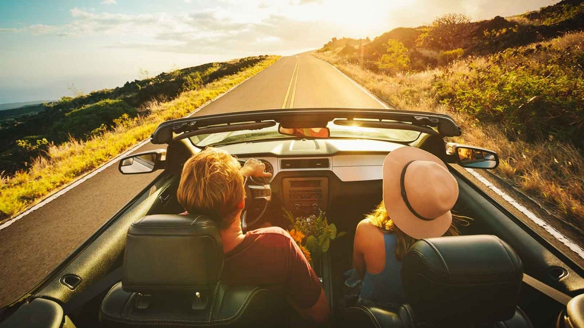 Friends on a road trip, driving down the highway in a convertible