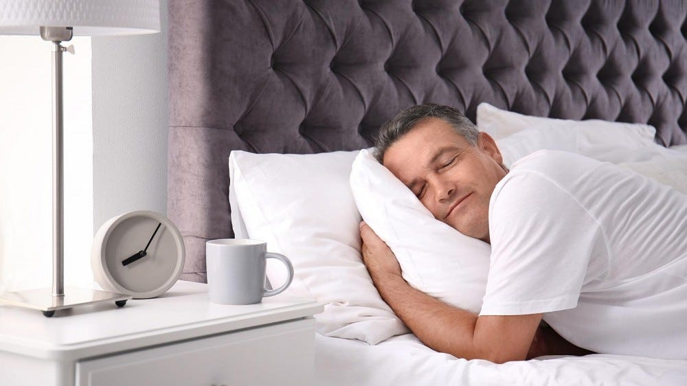 Man sleeping on a comfortable pillow in a stylishly decorated bedroom.