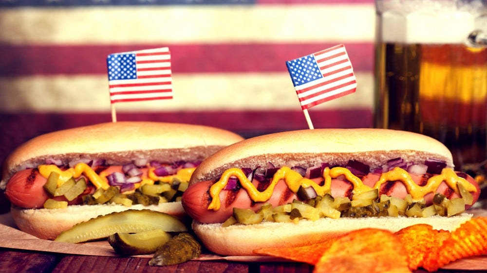 Two loaded hot dogs with American flag toothpicks in their buns.