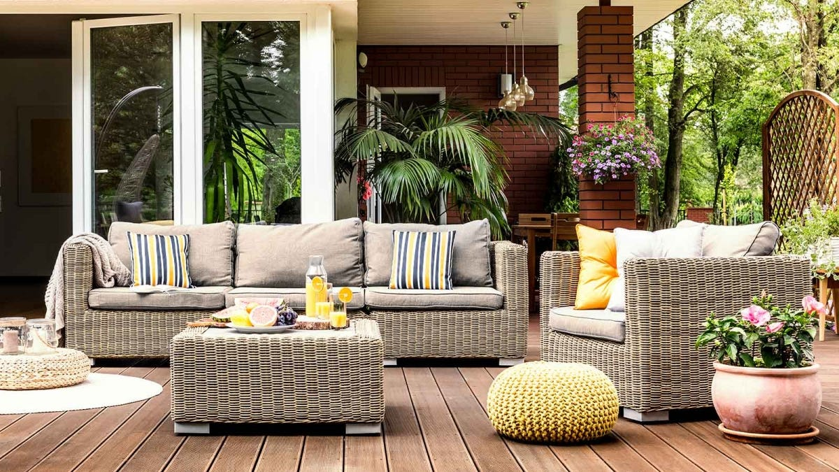 A lovely outdoor seating arrangement with plush pillows and colorful decorations.