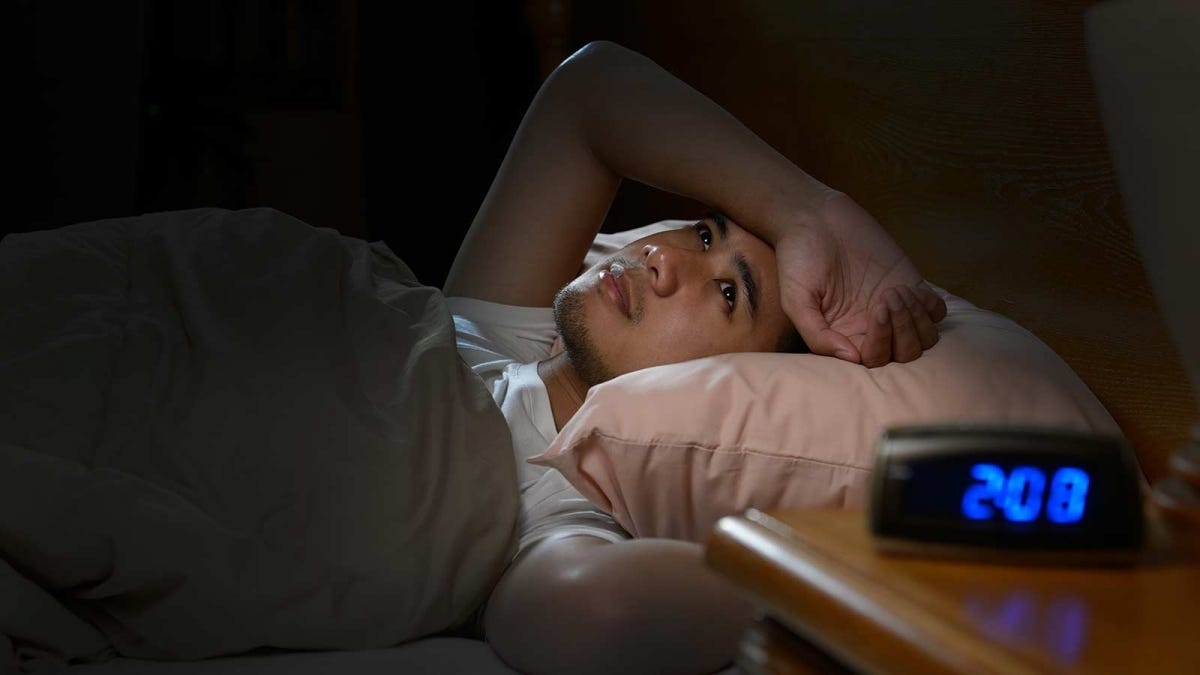 man staring at the ceiling, unable to sleep