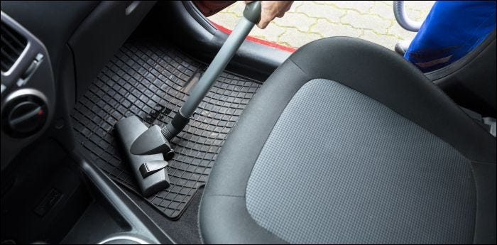 Close-up of person Vacuuming Car Mat With Vacuum Cleaner