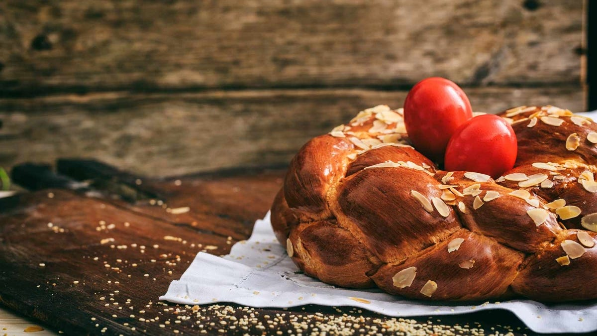 A loaf of Easter bread shaped like a braided nest with two red eggs resting in the center.