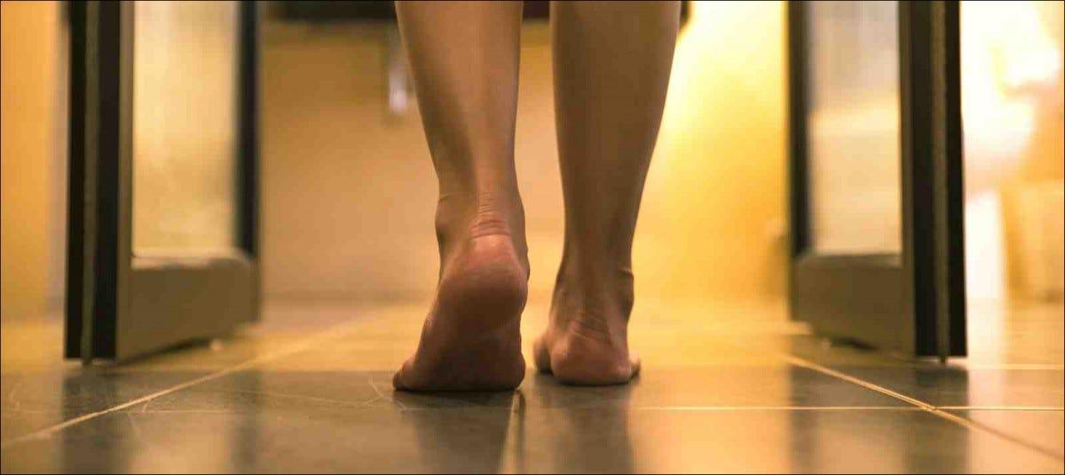 woman standing barefoot on tiled shower floor