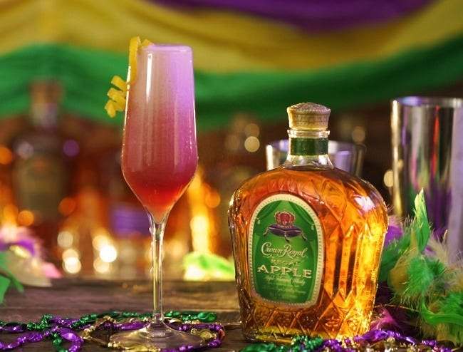 A Carnival Queen cocktail next to a bottle of Apple Crown Royal.
