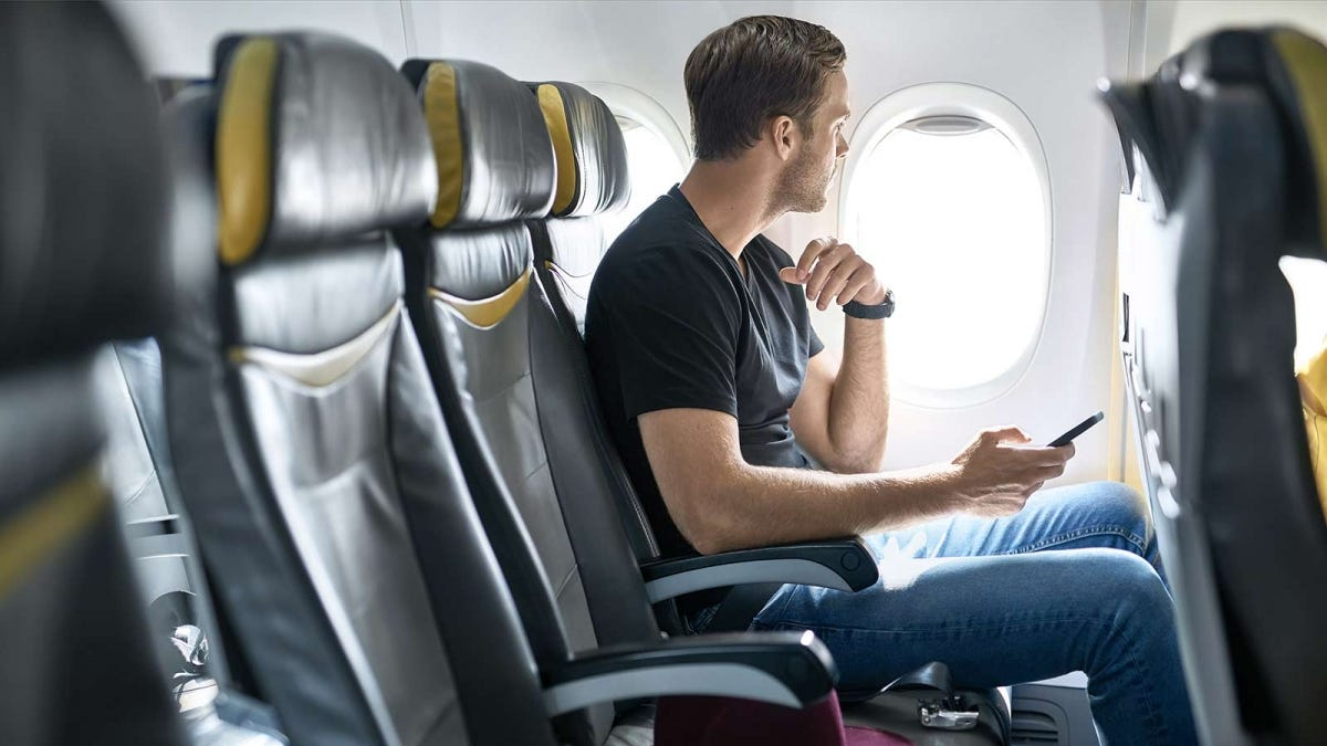 man looking nervously out the window of a plan before take off