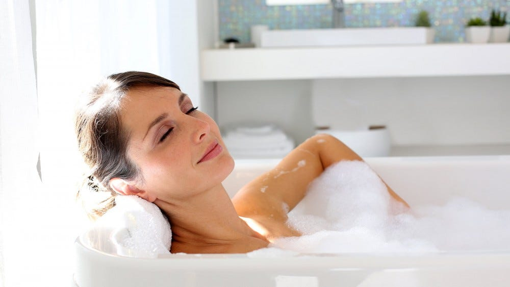 A woman relaxing in a bubble bath.