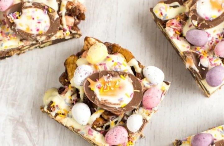 Four squares of Crème Egg Rocky Road, each topped with Cadbury mini eggs and a Cadbury Crème egg.