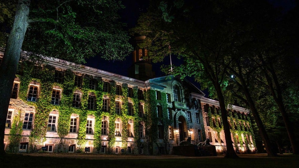 The campus of Princeton University, with ivy covered buildings, illuminated at night.