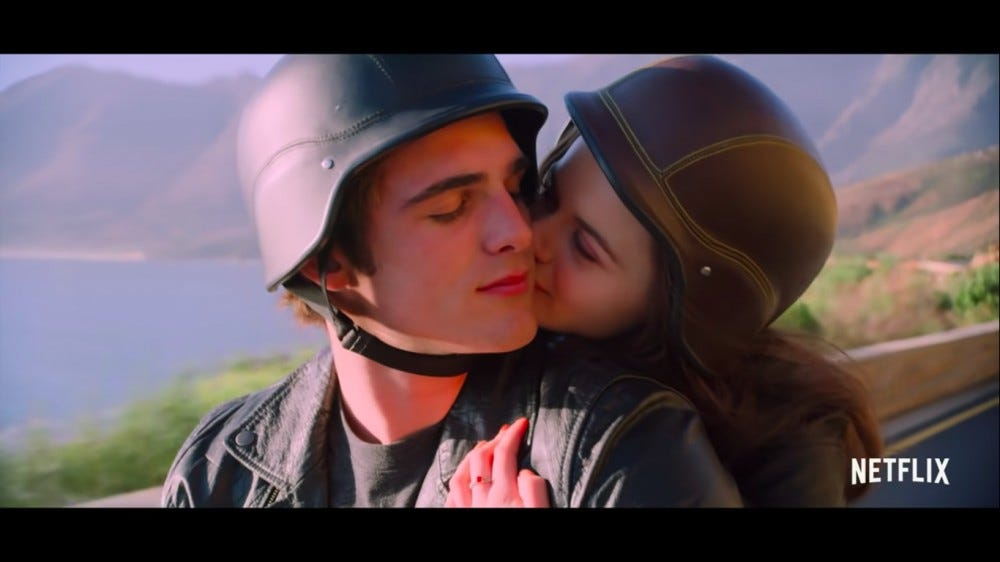 A couple on a motorcycle kiss.